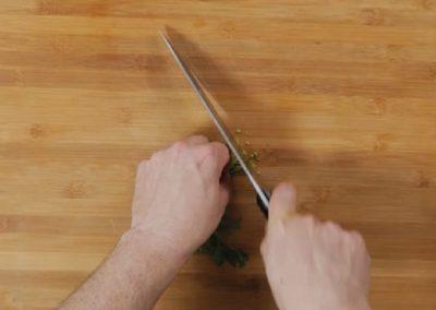1. Per prima cosa tritare finemente il gambo del prezzemolo e schiacciare poi con la lama di un coltello l'aglio.